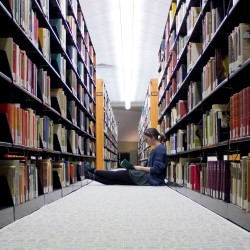 Student sitting in stacks reading